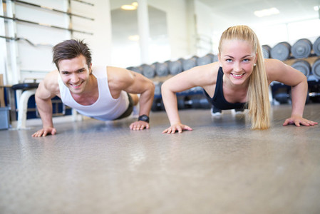 Happy Couple Doing Push Ups Together in Gym