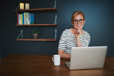 woman with laptop smiling at camera