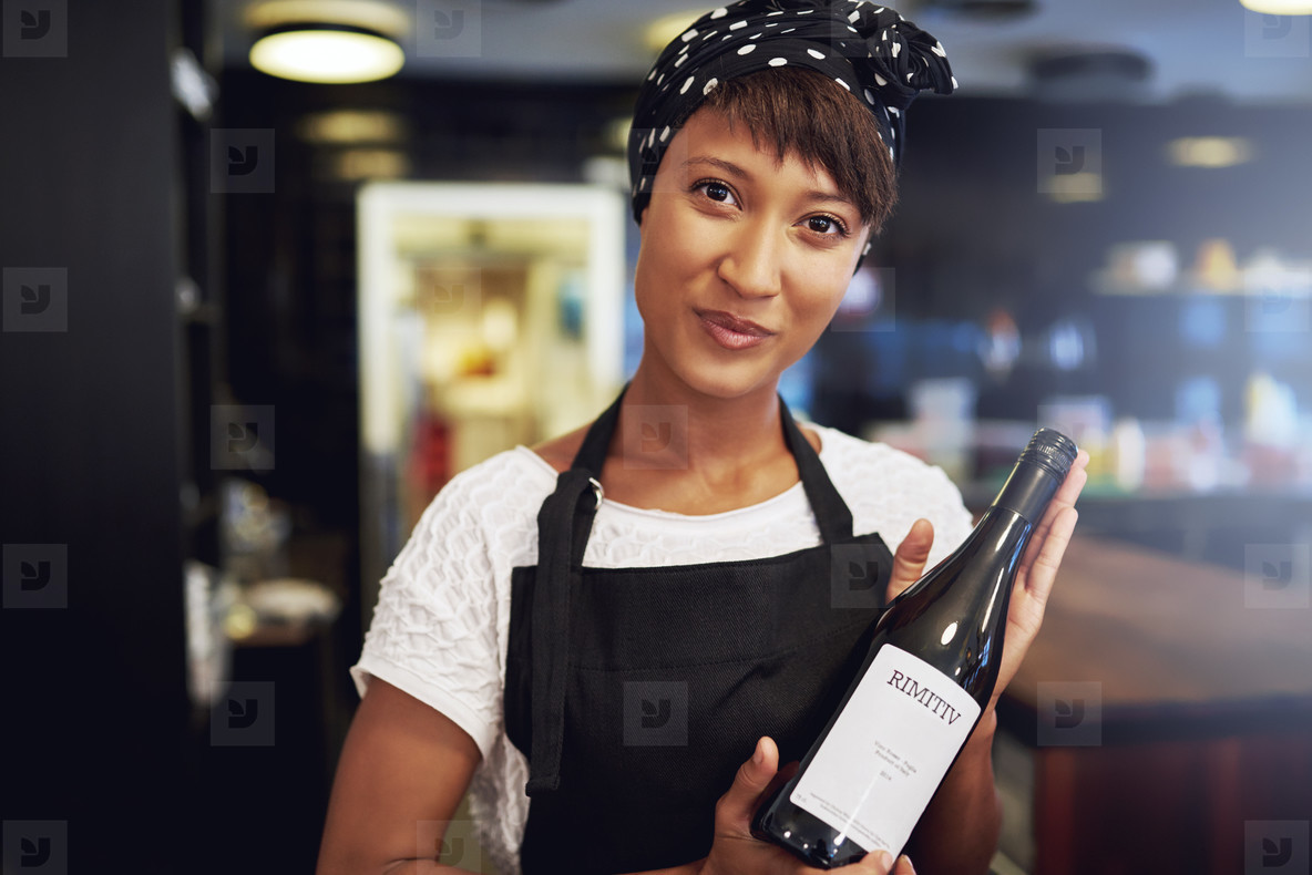 African American lady presenting a bottle of wine