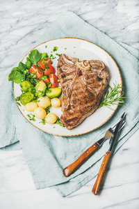 Cooked beef tbone steak with vegetables and rosemary