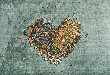 Various raw grains beans and cereals in shape of heart