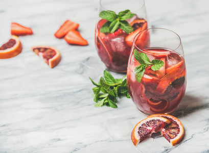 Fruit refreshing Sangria cocktails with ice cubes and fresh mint
