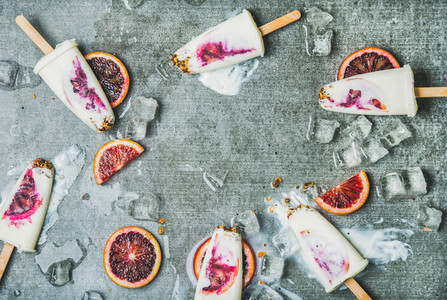 Orange  yogurt  granola popsicles on ice cubes  copy space