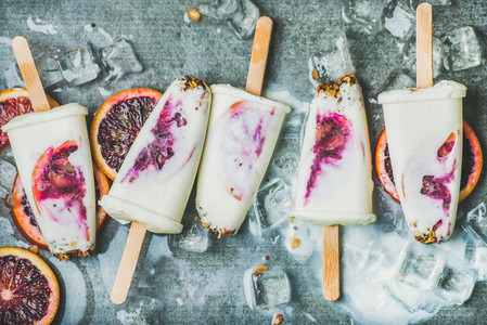Red orange  yogurt  granola popsicles on ice cubes  concrete background