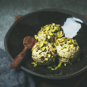 Homemade pistachio ice cream scoops with crashed nuts  square crop