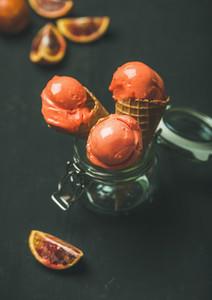 Refreshing summer blood orange ice cream in sweet waffle cones