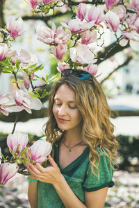 Young woman in casual clothes touching magnolia flowers