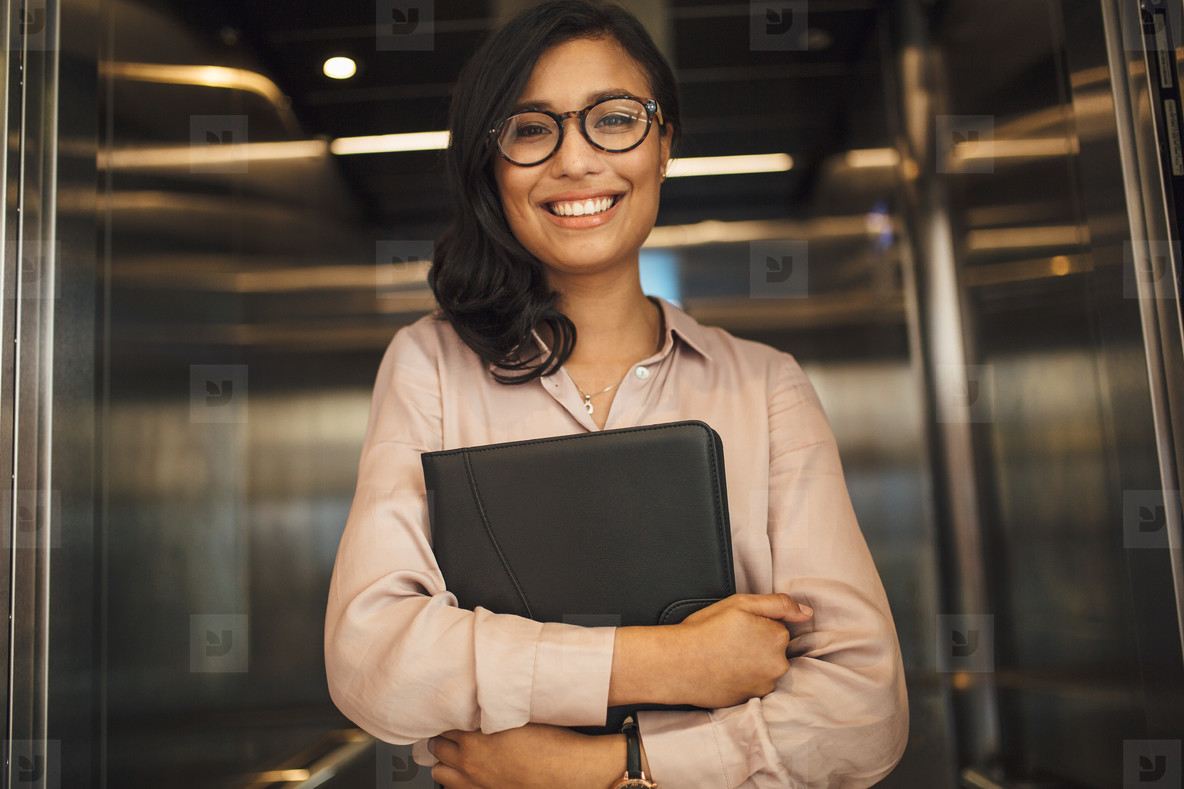 Smiling business woman in office elevator
