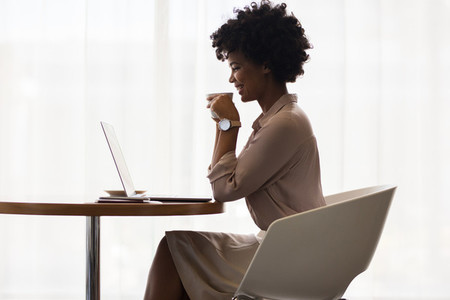 Smiling businesswoman drinking coffee and using laptop
