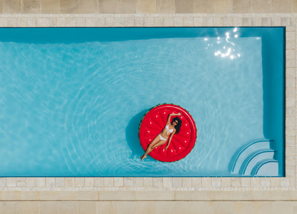 Young woman floating on inflatable mattress in pool