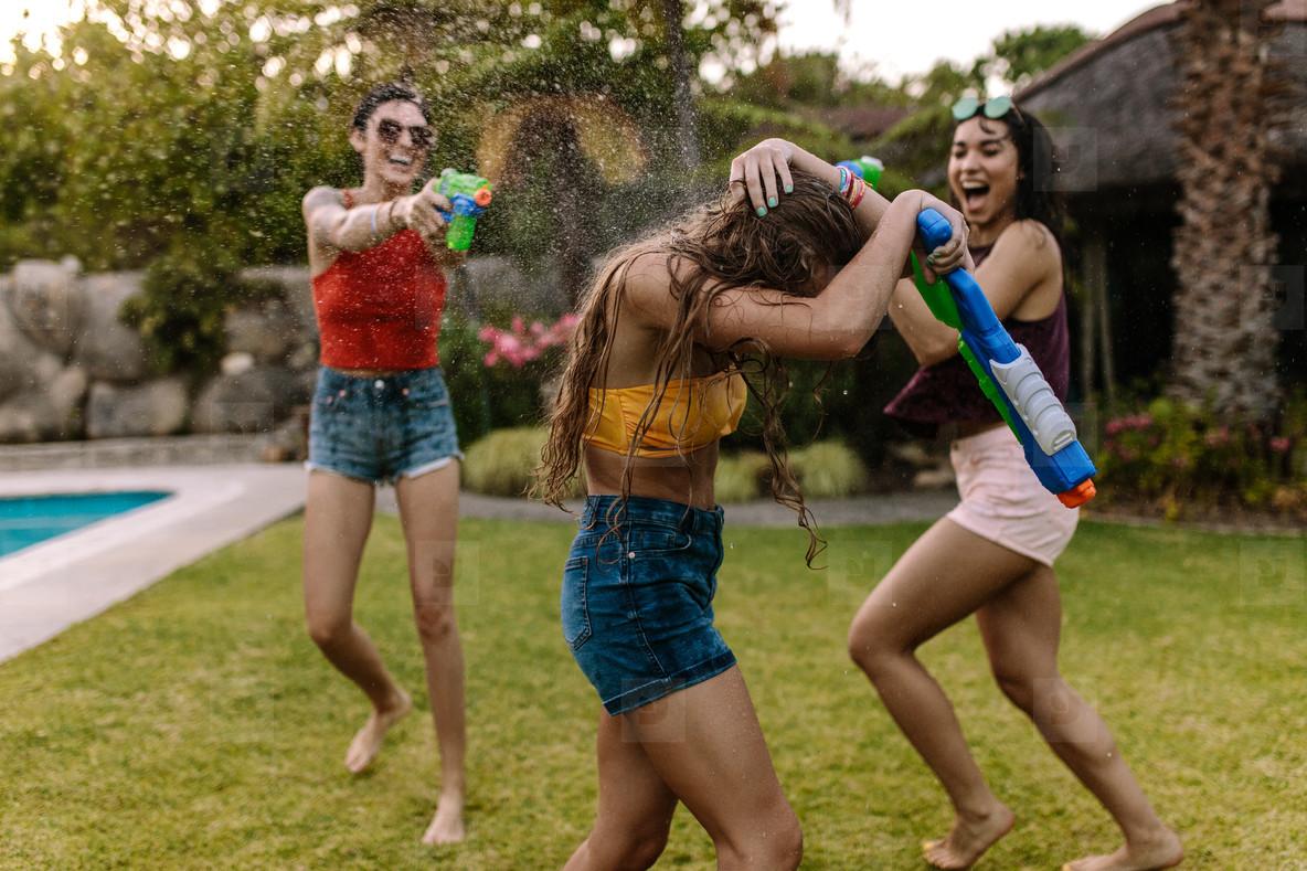 Crazy female friends having water gun battle