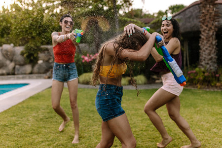 Crazy female friends having water gun battle