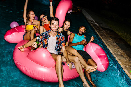 Friends hanging out at evening pool party