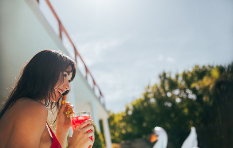 Smiling woman having a tropical drink at poolside