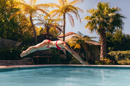 Woman in bikini diving into swimming pool
