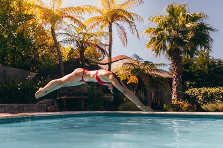 Woman in bikini diving into swimming pool