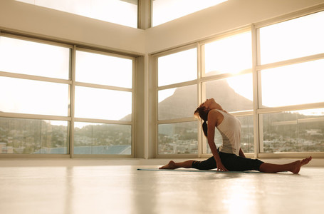 Woman doing a split on yoga mat