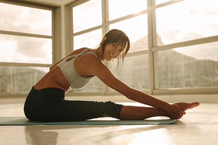 Smiling woman doing stretching workout
