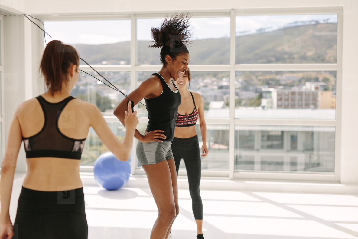 Woman jumping rope with friends in gym