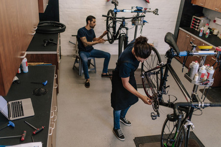 Two mechanics repairing  bicycles in workshop