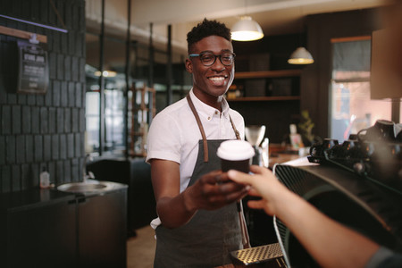 Barista serving customers inside a coffee shop