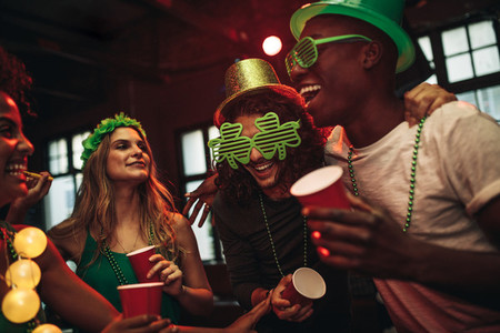 Multi ethnic friends celebrating St  Patricks Day in nightclub