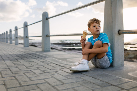 Boy eating an ice cream sitting near seafront