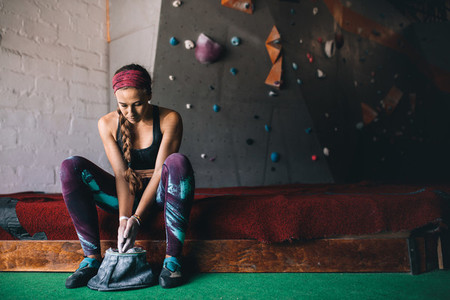Woman wall climber coating hands with gripping powder