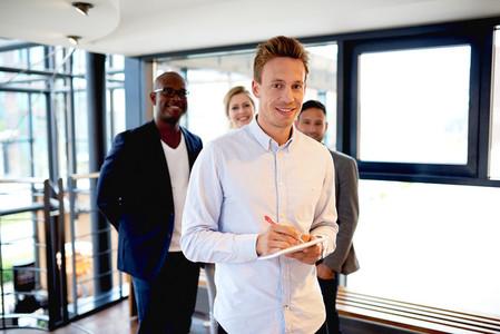 Group of young executives at work smiling and facing camera