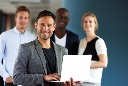 Young white executive holding laptop with colleagues in background