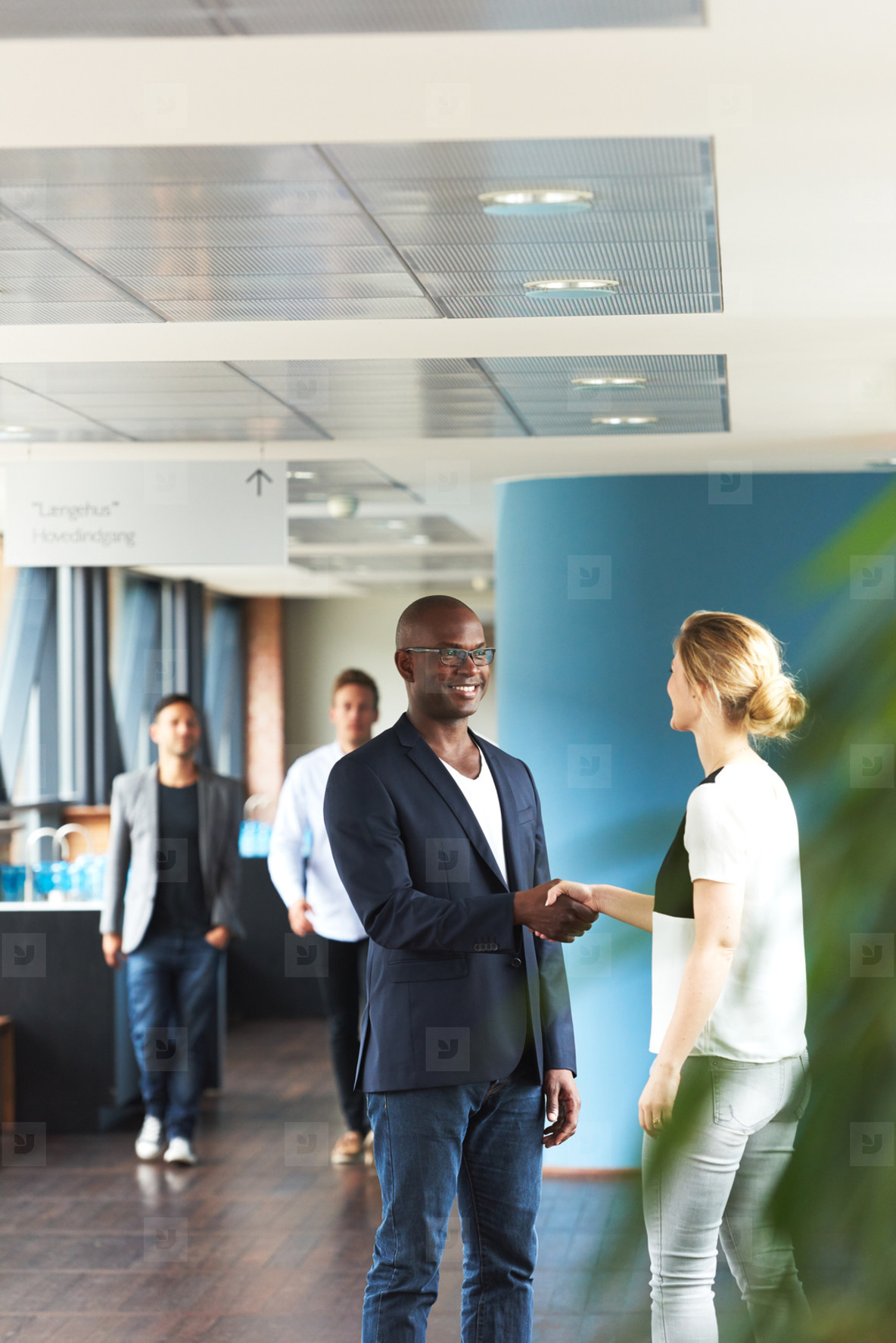 Black man and white woman shaking hands in office