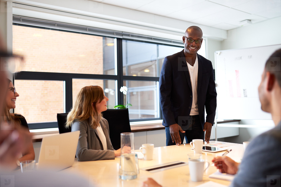 Black male executive standing and leading a work meeting