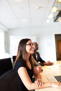 Profile of white female executive smiling during meeting