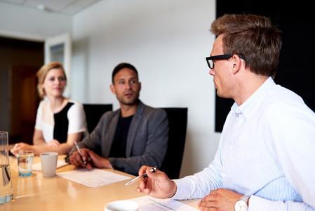 Young executives facing eachother during meeting