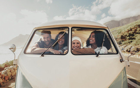 Group of friends on roadtrip sitting inside minivan