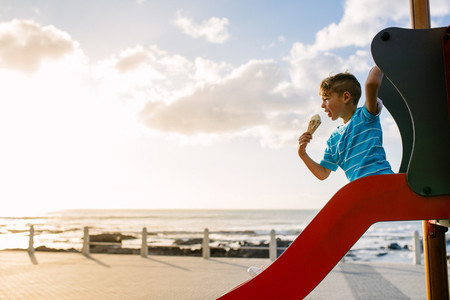 Boy eating an ice cream sitting on a slide