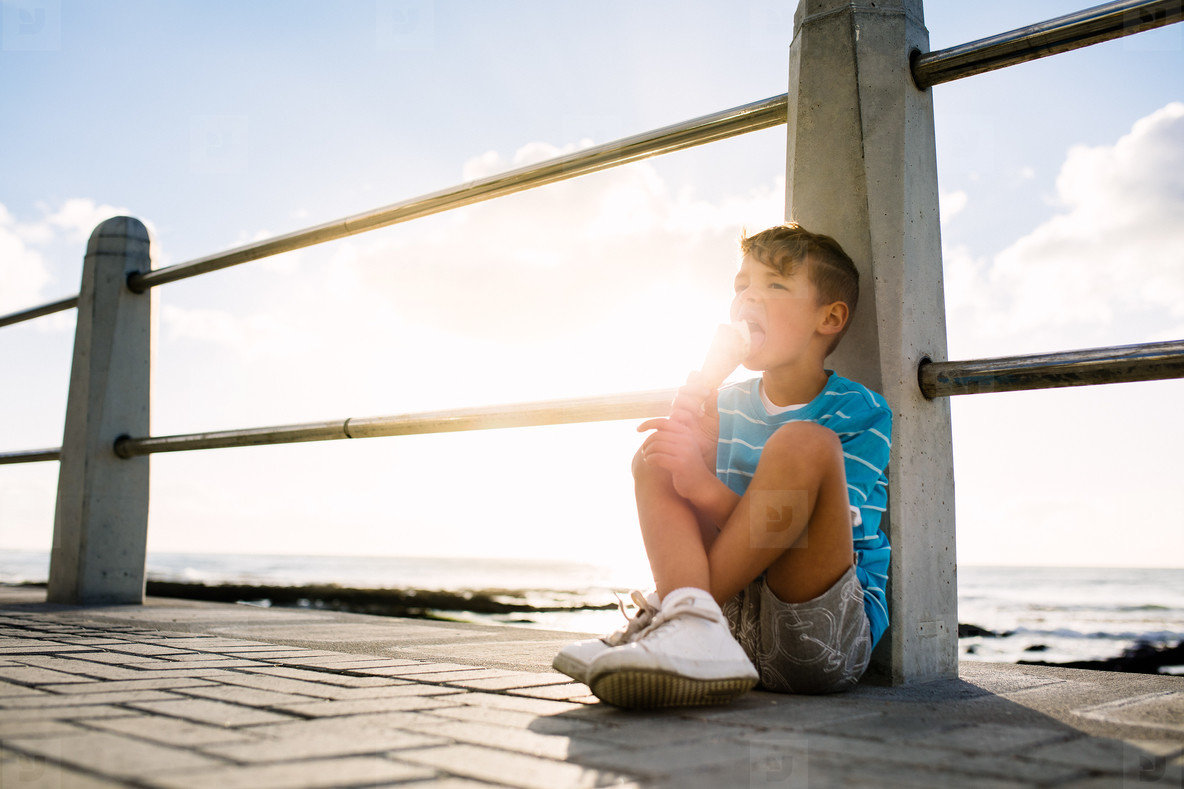 Boy eating an ice cream sitting near seashore