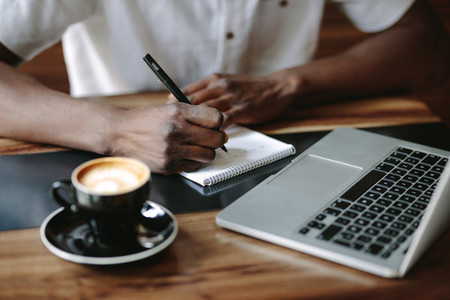 Man writing notes sitting at a coffee shop with a laptop on the