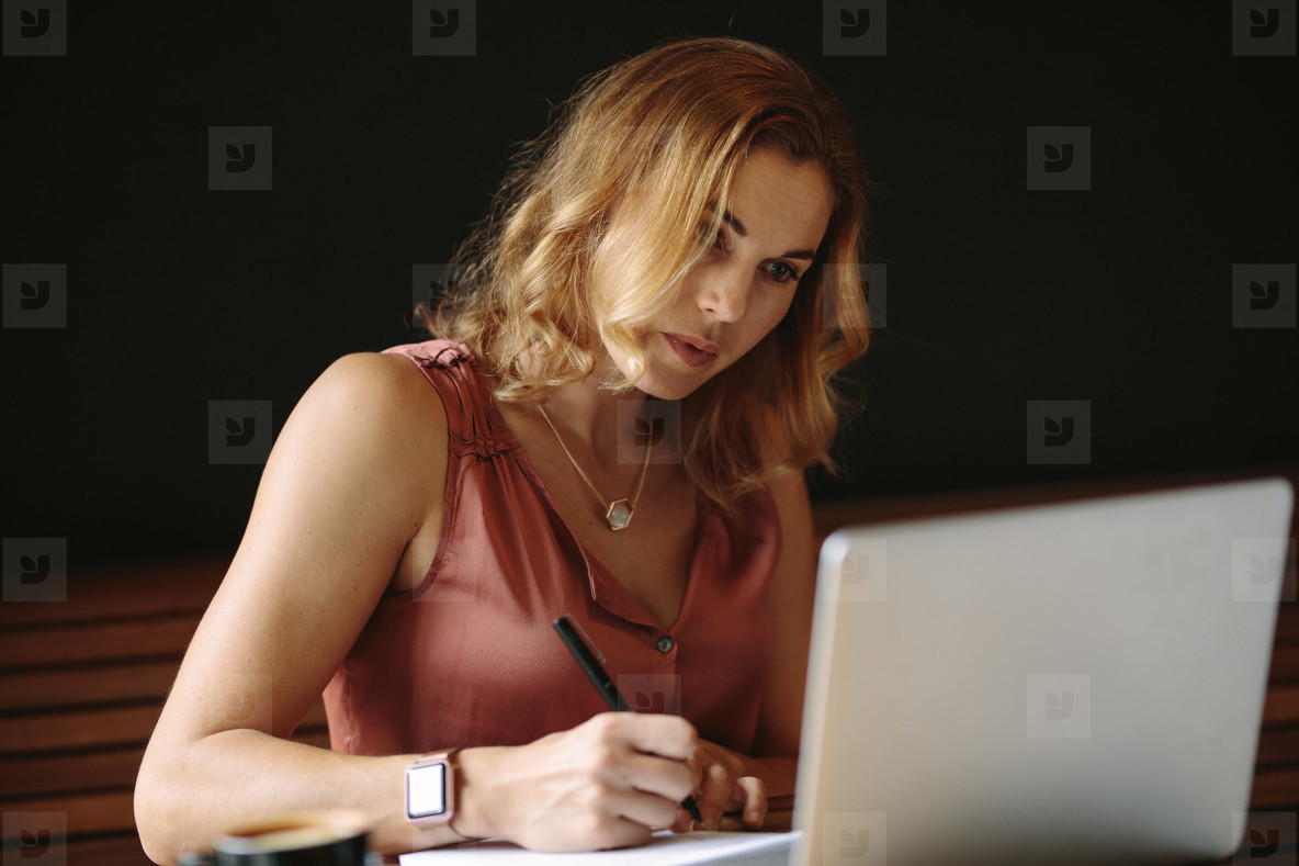 Woman working on a laptop computer at a coffee shop