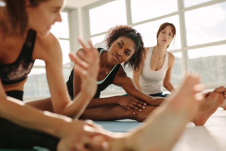 Women during yoga class break at gym