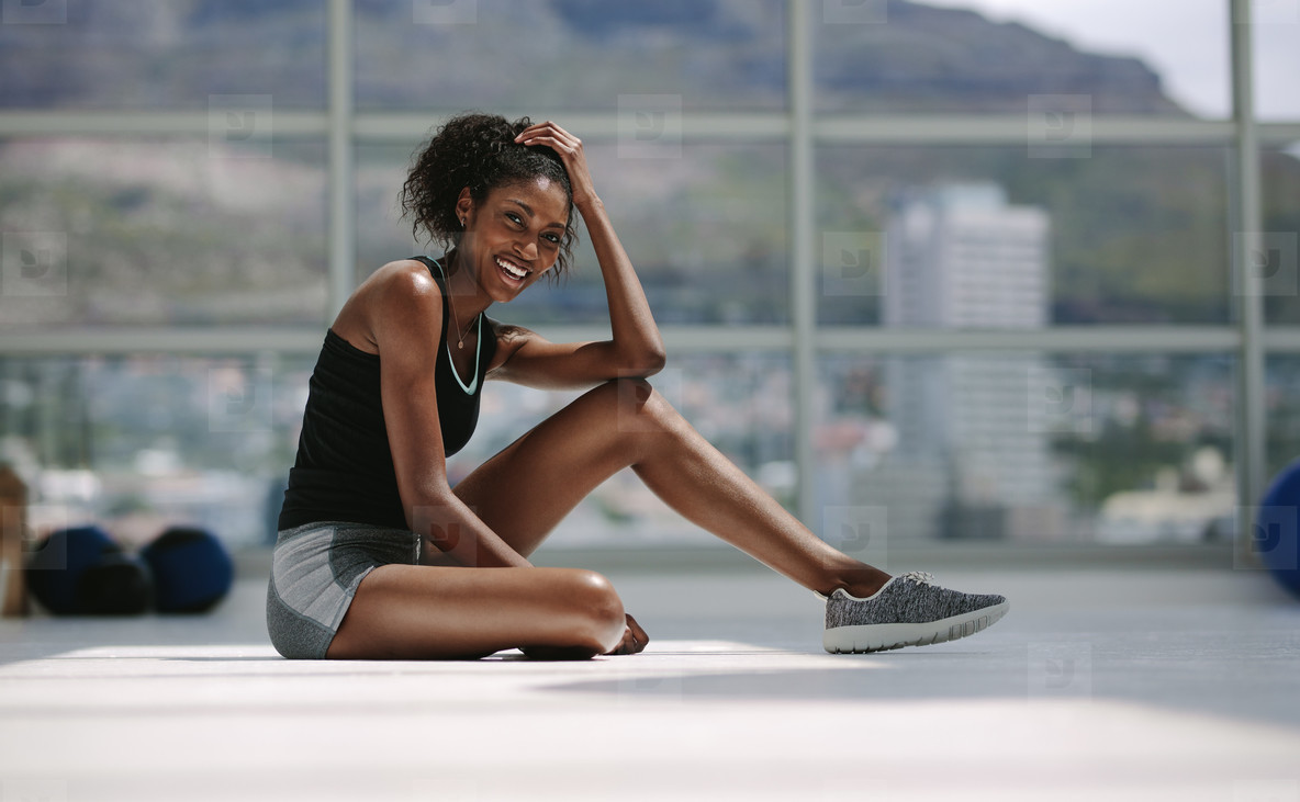 African woman relaxing after her workout at gym