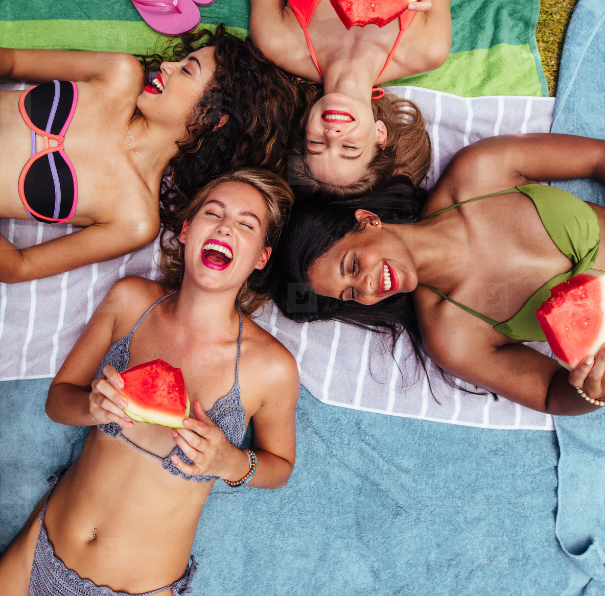 Cheerful friends lying by poolside with watermelon