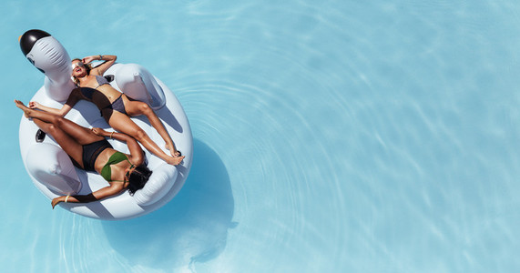 Woman sunbathing on floating pool inflatable toy