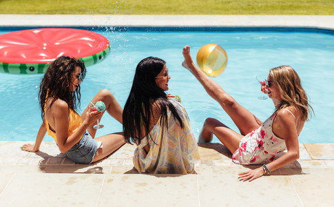 Female friends having party by the swimming pool