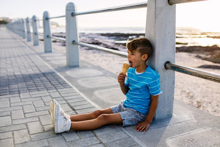 Boy eating an ice cream sitting near seashore