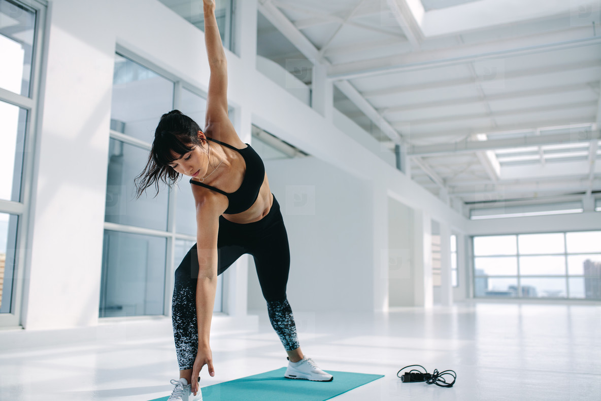 Healthy woman practising triangle yoga pose in gym