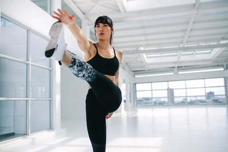 Woman doing yoga exercises at health club