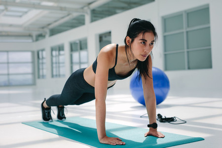 Strong woman doing push ups on mat
