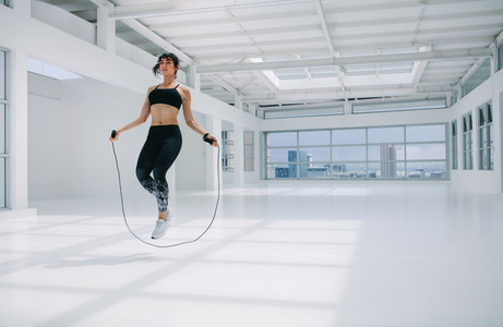 Woman skipping rope in fitness studio