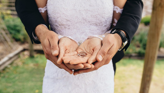 Wedding rings in hands of groom and bride